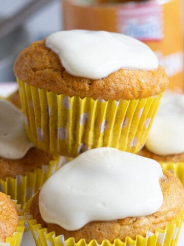 A stack of pumpkin muffins in a cake stand.