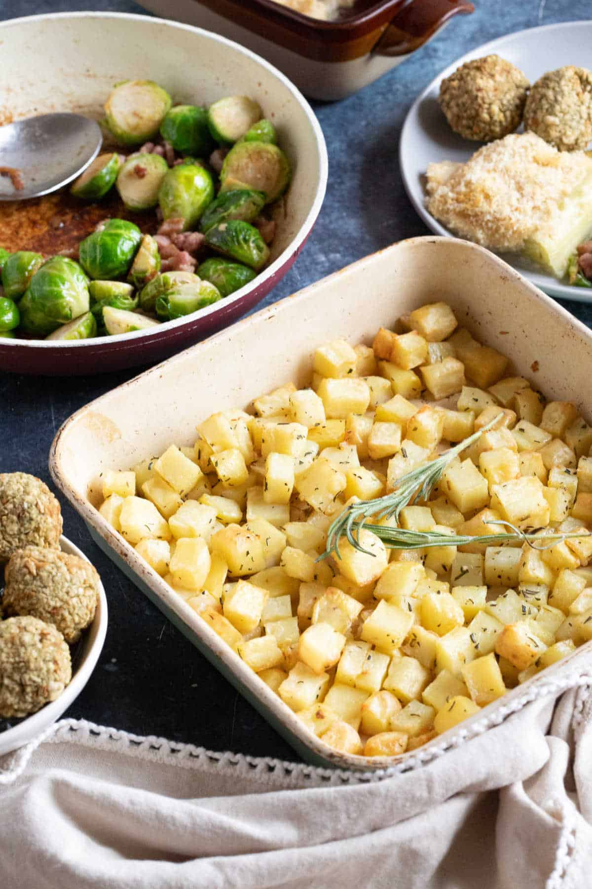 Parmentier potatoes with garlic and herbs in a roasting tin.