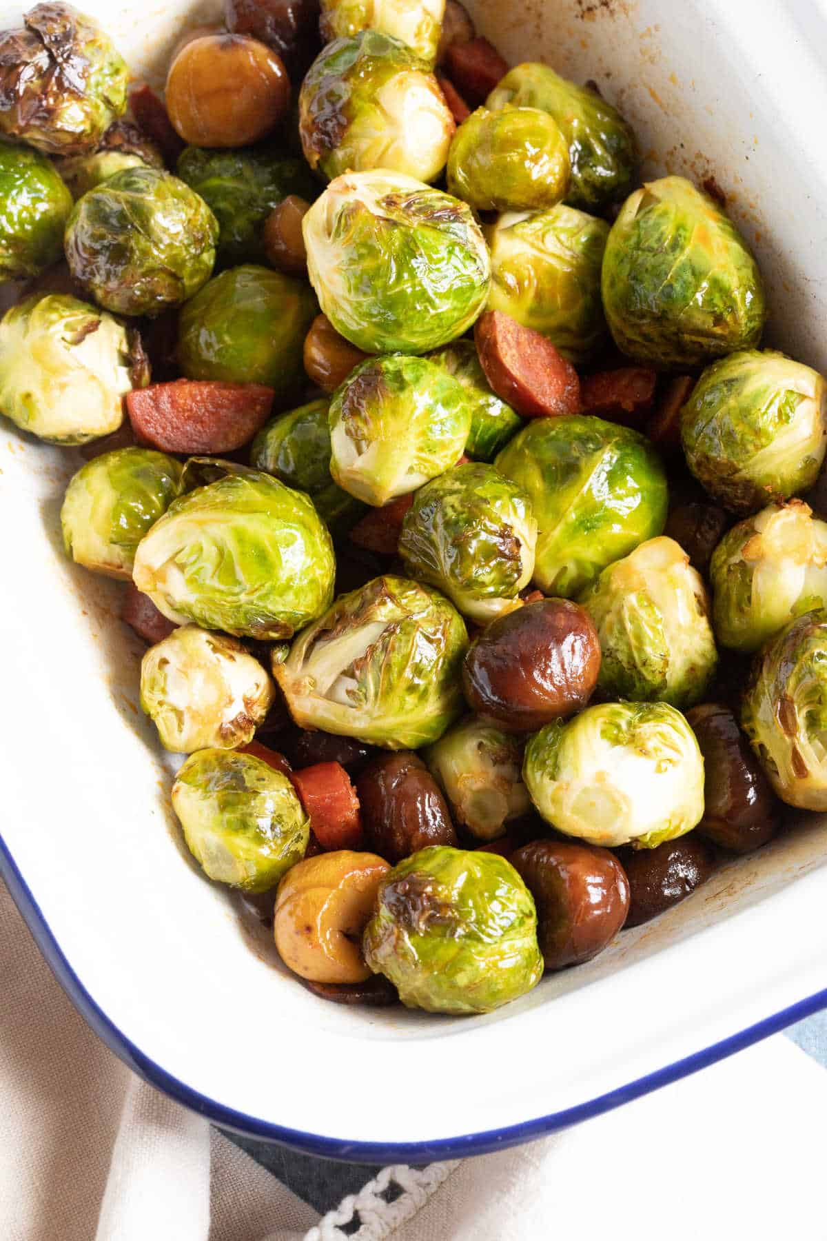 Roasted Brussels Sprouts in a white baking tin with chestnuts and chorizo.