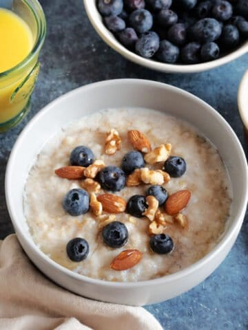 A bowl of slow cooker porridge with blueberries.